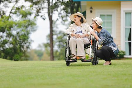 高齢の女性が娘と一緒に裏庭で車椅子でリラックスします。 写真素材
