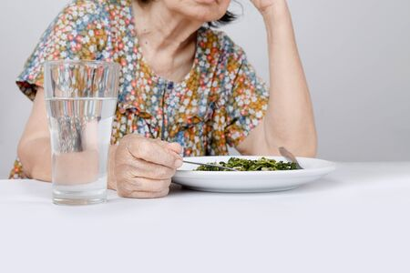 disgusted: Elderly asian woman bored with food Stock Photo