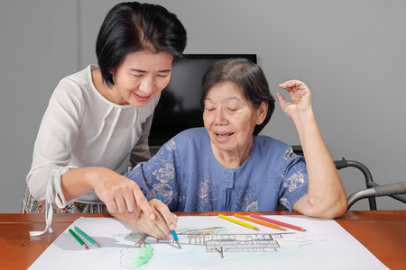 Elderly woman painting color on her drawing with daughter , hobby at home
