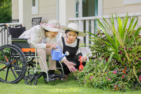 Elderly woman gardening in backyard with daughter
