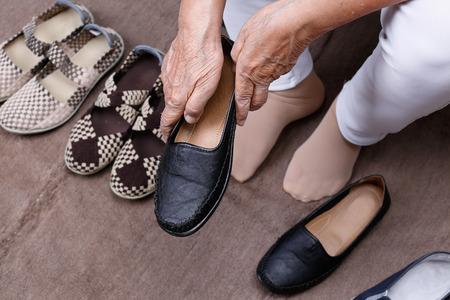 Anciana, ponerse los zapatos Foto de archivo