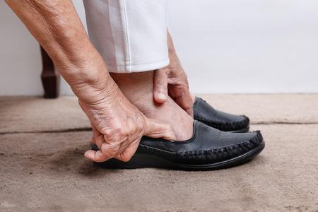 mujer mayor que pone en los zapatos