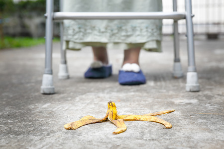 Careless elderly woman step over a banana peel on walkway Stock Photo