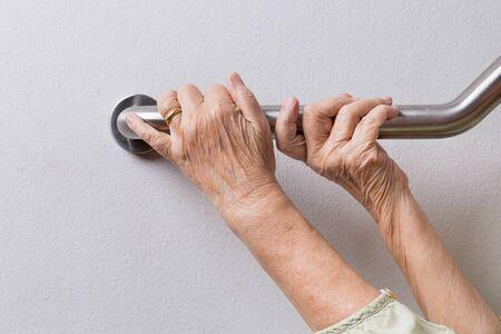 Donna anziana che tiene sul corrimano per passi di sicurezza