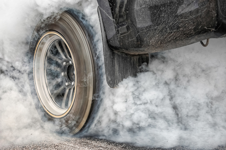Drag racing car burns rubber off its tires in preparation for the race Imagens