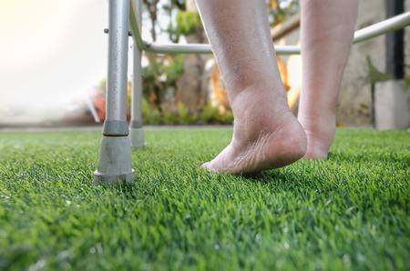 Elderly woman bare swollen feet on grass with walker