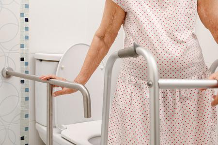 Ältere Frau , die auf Handlauf in der Toilette hält