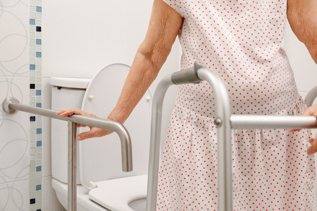 Elderly woman holding on handrail in toilet.