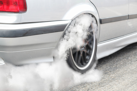 Drag racing car burns rubber off its tires in preparation for the race Stock fotó