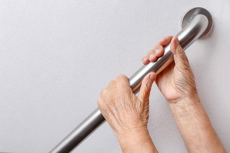 Donna anziana che tiene sul corrimano per passi di sicurezza a piedi