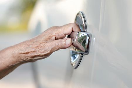 elderly woman hand opening car door Reklamní fotografie