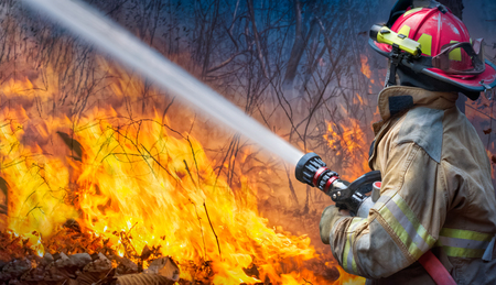 Natural disaster ,firefighters spray water to wildfire. 写真素材