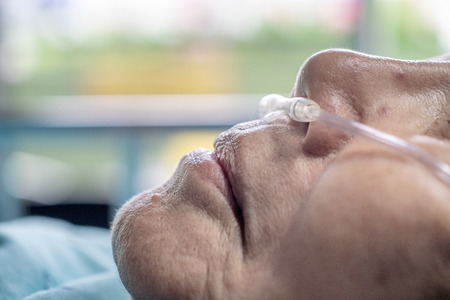 Elderly woman with nasal breathing tube to help with her breathing Фото со стока