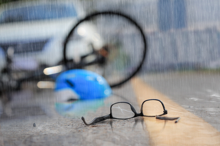 Accident car crash with bicycle on road in rainy weather