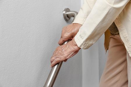 Donna anziana che tiene sul corrimano per i passaggi di sicurezza a piedi Archivio Fotografico