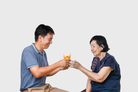 Elderly woman getting a glass of iced tea from son