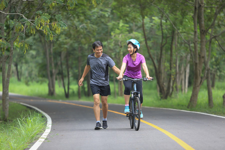 Middle aged couple walking with their bicycle in park