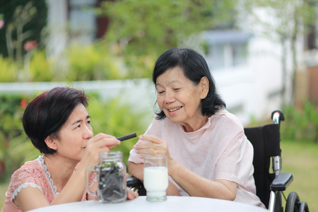 Daughter caring for the elderly Asian woman, picking a chocolate cookie to mother in backyard. Archivio Fotografico