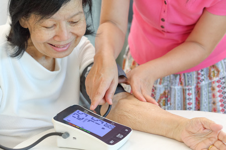 Daughter checking blood pressure (hypertension) of elderly mother at home Stockfoto