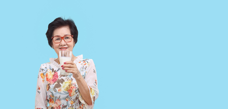 Senior woman holding a glass of milk, isolated on white background.