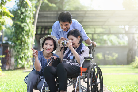 Son and daughter in law looking after elderly mother in backyard