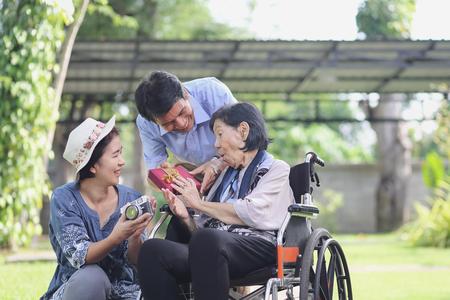 Hijo y nuera regalo madre anciana en el patio trasero Foto de archivo