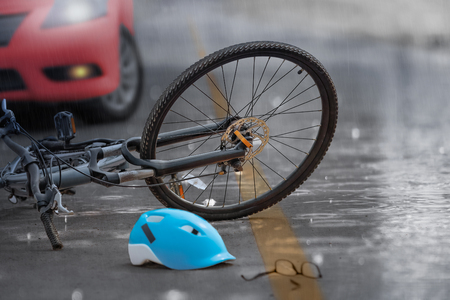 Accident car crash with bicycle on road ,rainy day. Stock Photo