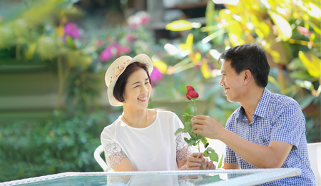 Asian middle-aged man gives a rose to his wife in valentine day Stockfoto
