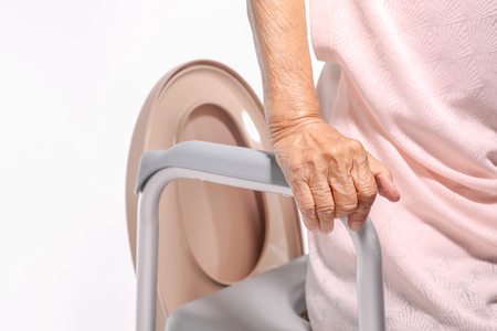 Elderly woman using mobile toilet seat chair