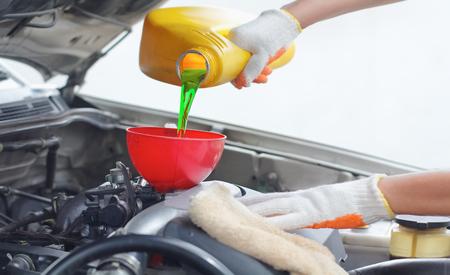 Car mechanic pouring new oil to engine. Reklamní fotografie