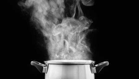Dampf über Kochtopf in der Küche auf dunklem Hintergrund