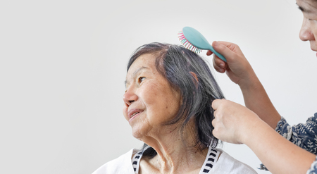 elderly woman combing hair by caregiver