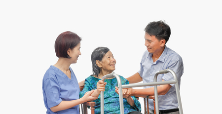 Son looking after elderly mother on wheelchair with caregiver 版權商用圖片