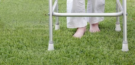 Elderly woman walking barefoot therapy on grass in backyard. Banco de Imagens