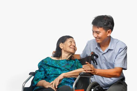 Son looking after elderly mother on wheelchair