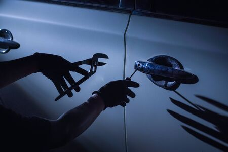 Car thief using a tool to break into a car Banco de Imagens