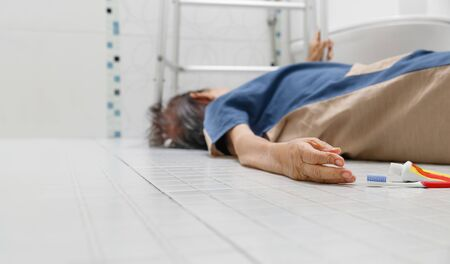 Elderly woman falling in bathroom because slippery surfaces Banco de Imagens