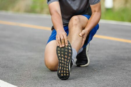 Male middle aged having a cramp while jogging. Stop and massage calf