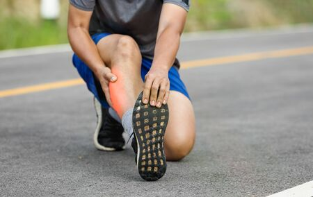 Male middle aged having a cramp while jogging. Stop and massage calf Stock Photo - 128115160