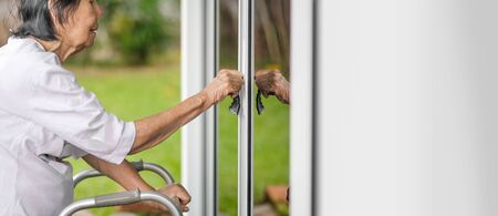 Elderly woman with key opening front door.