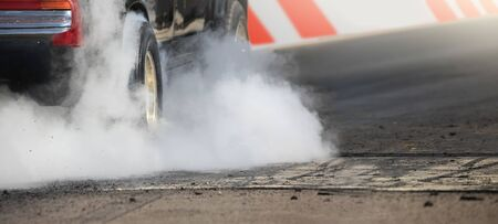 Drag racing car burns rubber off its tires in preparation for the race Banco de Imagens