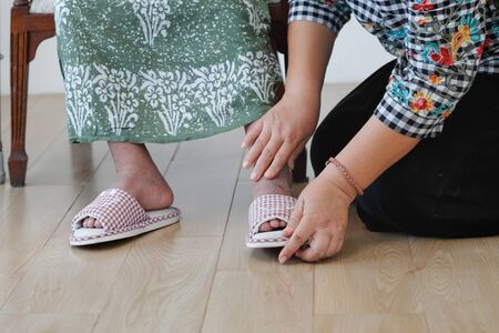 Elderly woman putting on the slipper by daughter