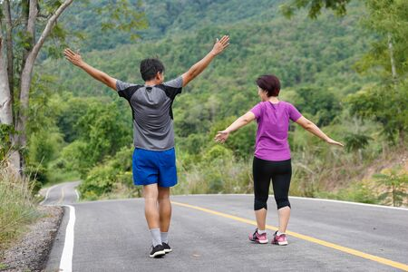 Asian middle aged couple stretching muscles before jogging in park