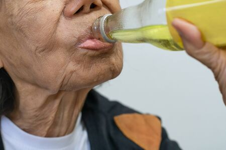 elderly asian woman drinking mineral lemon