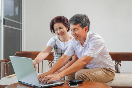 Middle aged asian couple using laptop at home