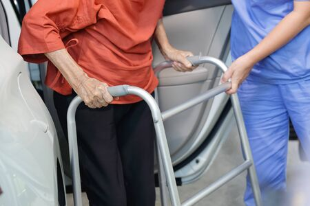 Elderly female using walker while get out of car with caregiver