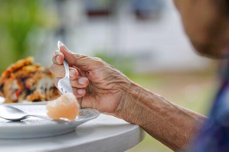 ältere Frau frühstückt im Hinterhof