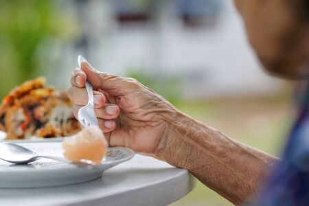 femme âgée prendre son petit déjeuner dans l'arrière-cour