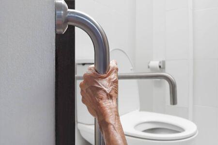 Elderly woman holding on handrail in bathroom Imagens