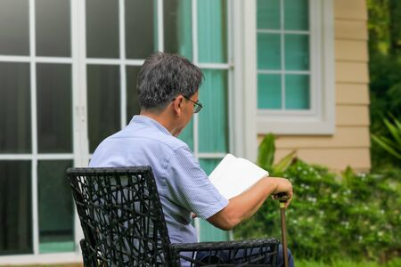 Senior male reading and relax in backyard